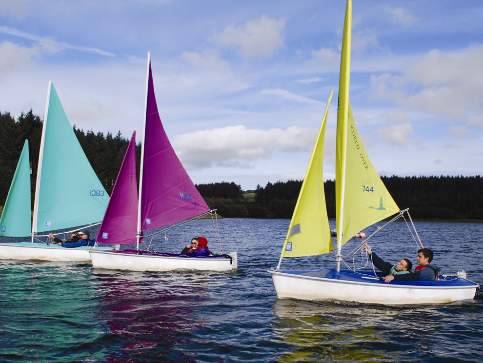 Three boats in a row with people in them, with different coloured sails, being sailed in water