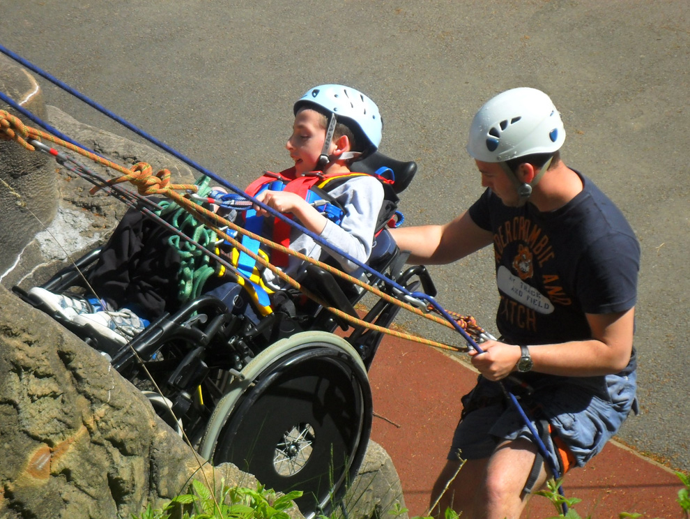 Boy in a wheelchair and carer abseiling down outdoor climbing wall with specialised harnesses and safety ropes