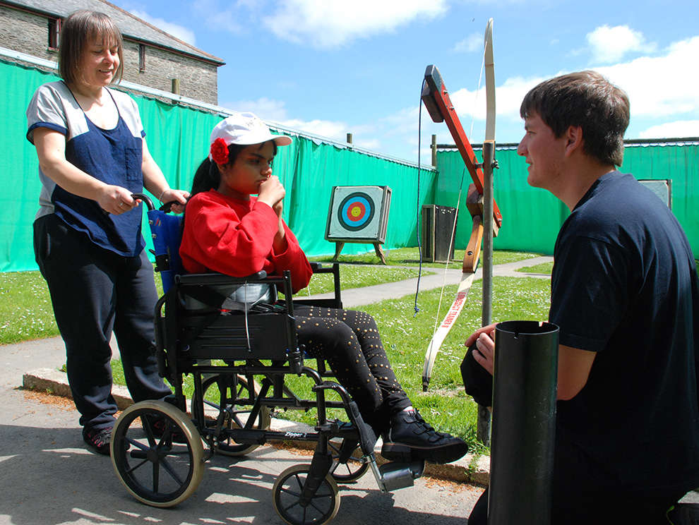 Activities instructor talking to girl in wheelchair with carer behind, outdoor archery range and equipment in background