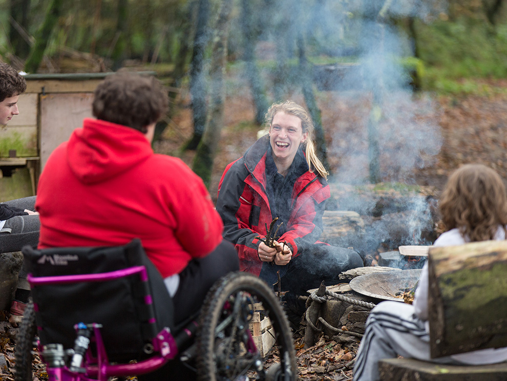 Three people outdoors around a smoking campfire, one in a wheelchair, one laughing and holding a bunch of twigs