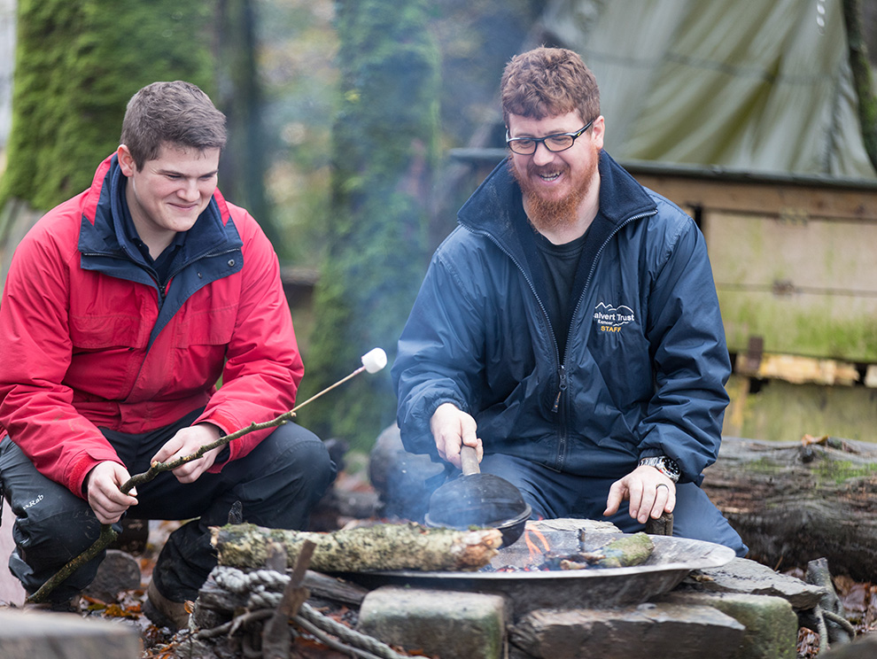 Two men, Calvert Trust Exmoor activities instructors smiling, sitting round a campfire cooking marshmallows