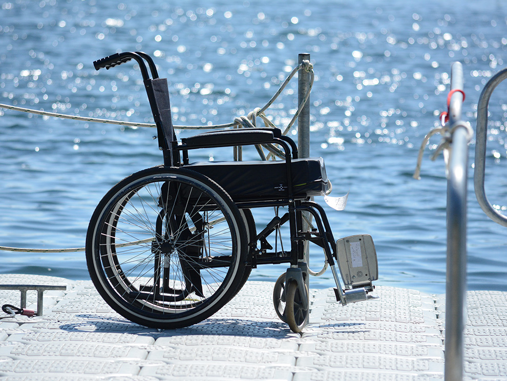 Empty wheelchair on a pontoon with water in the background on a sunny day