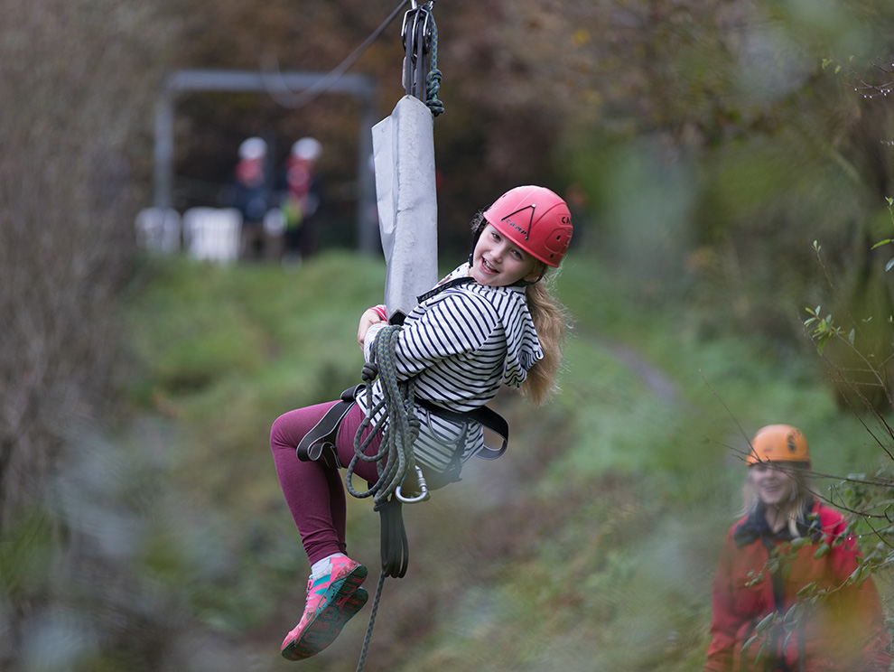 A girl in a harness and a helmet riding on a zipwire smiling and looking straight at the camera