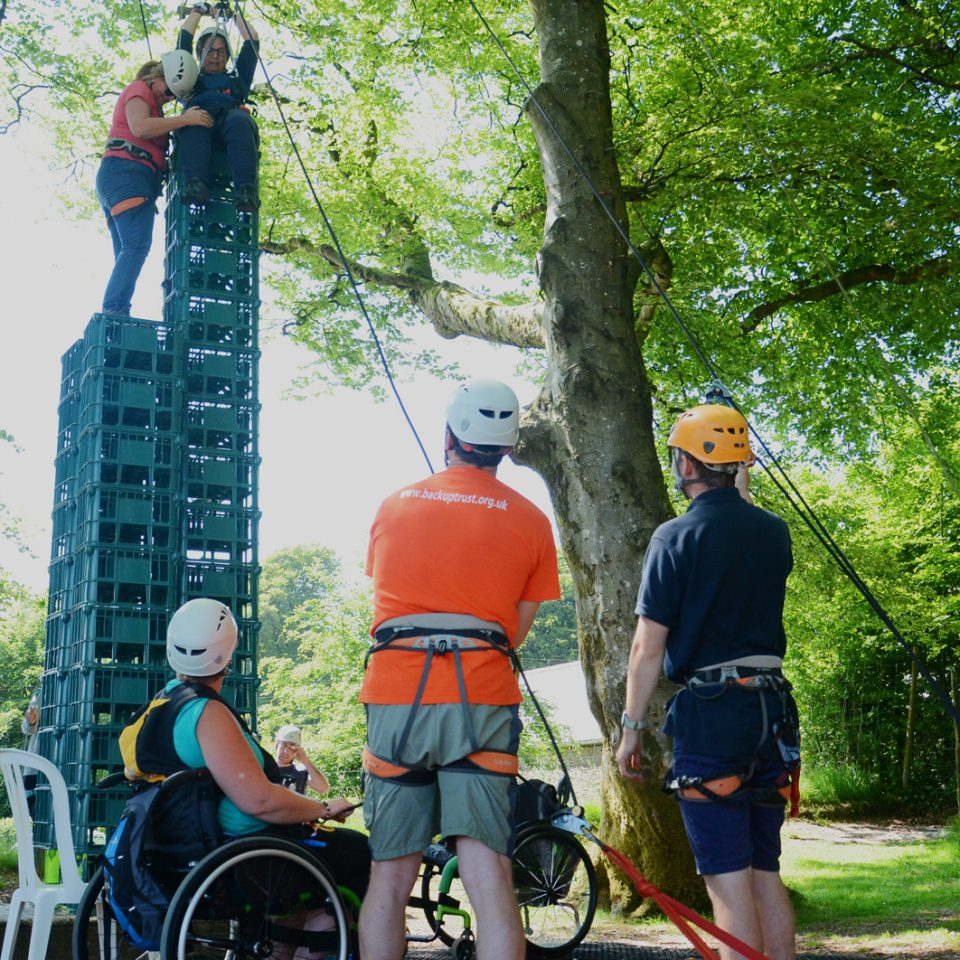 Two people building and standing on a crate stack tower outside, others watching, including two people in wheelchairs
