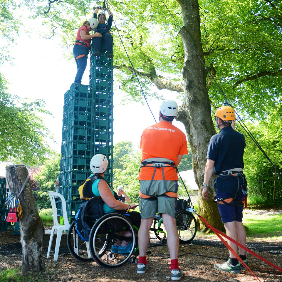 Two people wearing harnesses, building and standing on a crate stack tower amongst trees, others watching, one in a wheelchair
