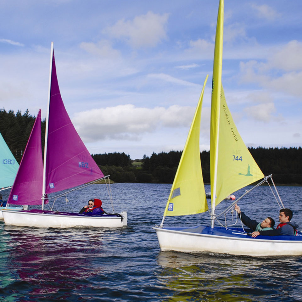 People in two colourful sailing boats on a reservoir