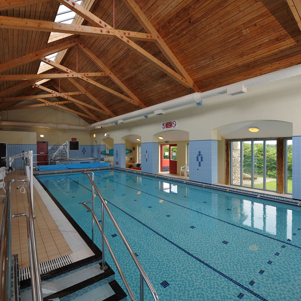 View of indoor swimming pool with hot tub and hoisting arms