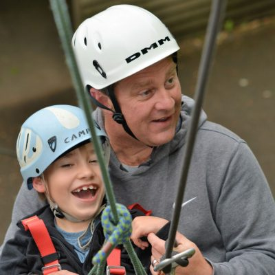 Man and boy abseiling with helmets, adaptive harnesses and ropes, looking happy