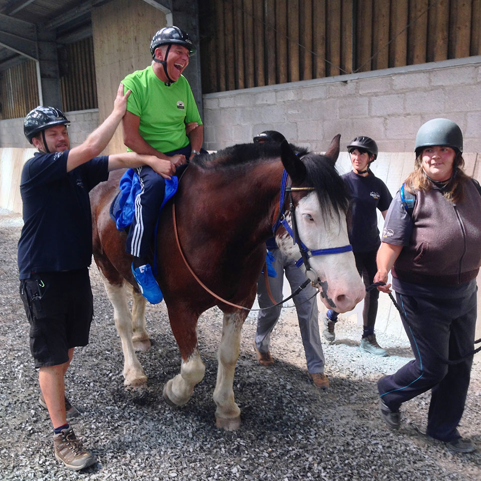 Man with disability riding a horse in indoor menage with riding instructors walking alongside