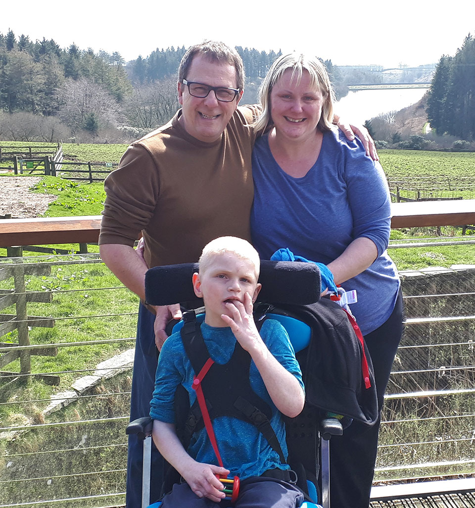 Man, woman and child in wheelchair posing on balcony in front of reservoir and country scenery