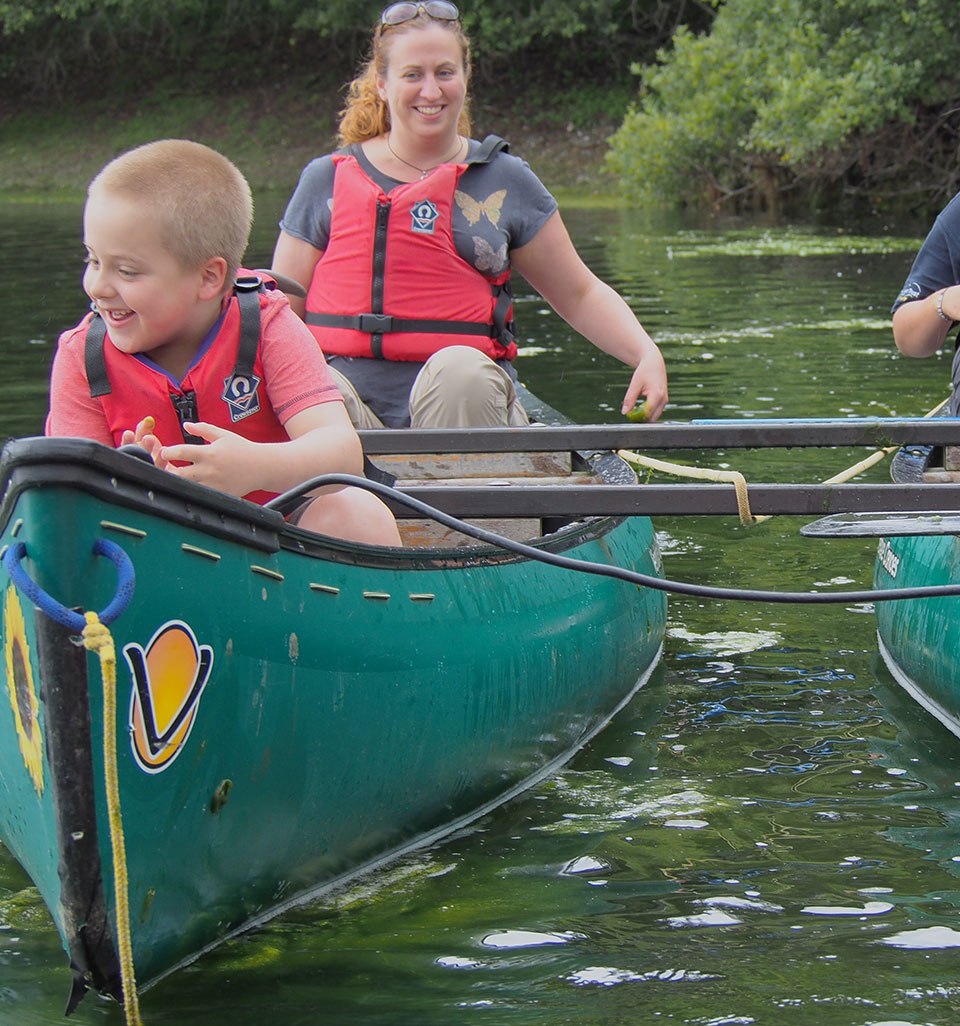 Smiling woman and boy wearing life jackets, sitting in a canoe on the water