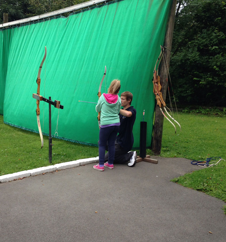 Instructor and child doing archery