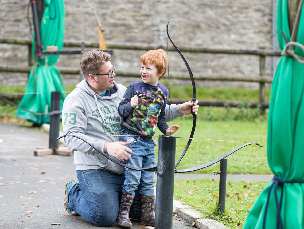 Man and child doing archery outside, child laughing