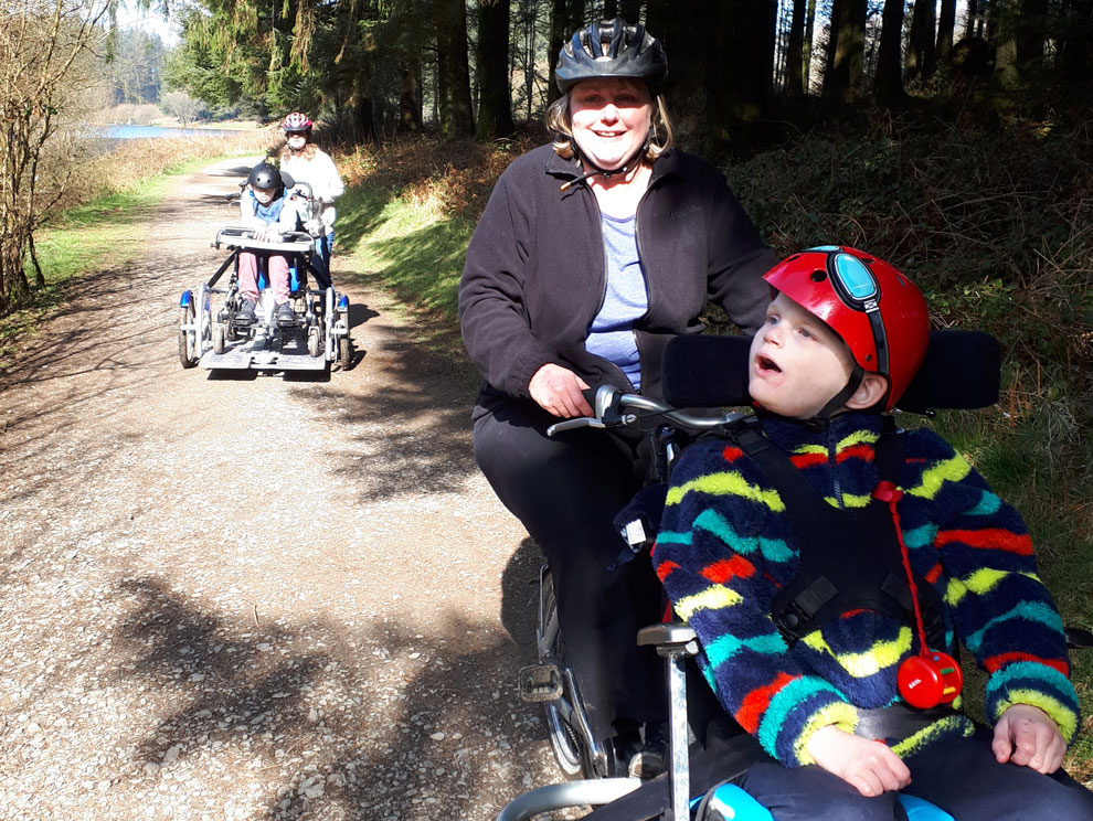 Two adults cycling outdoors on specialised adaptive biking equipment with disabled children wearing helmets