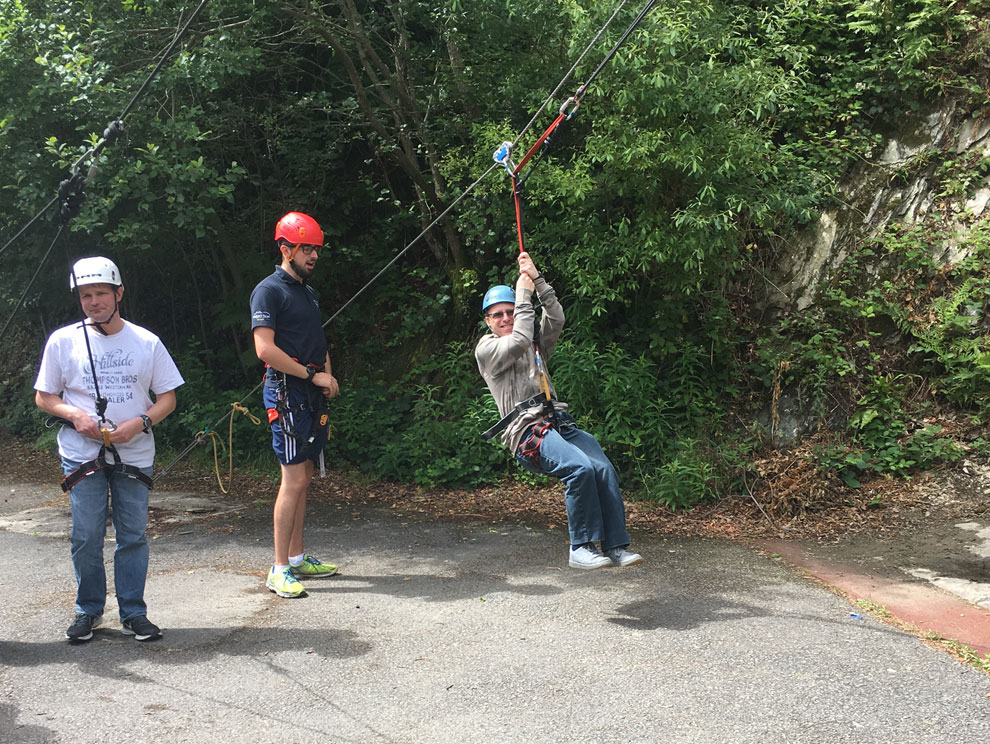 Two guests with learning disabilities and an activity instructor using outdoor climbing and hoisting equipment, ropes and harnesses, all wearing climbing helmets