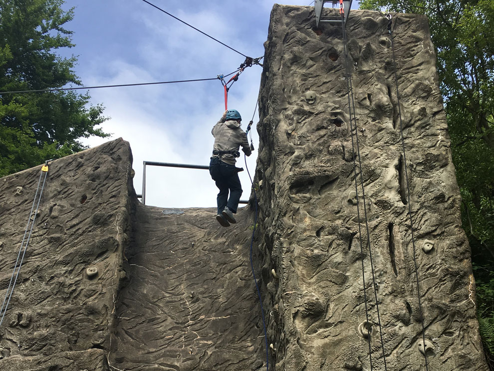 Person wearing climbing helmet and harness, suspended from sling on outdoor rock climbing wall with ropes and carabiners