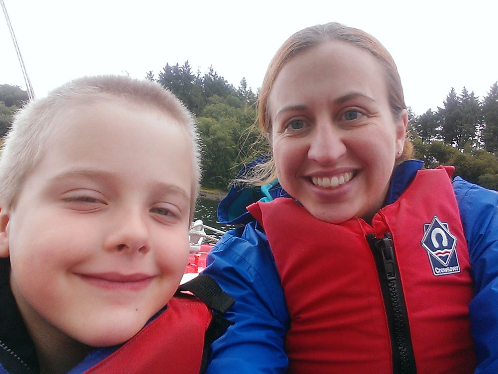 Woman and child selfie by the water, smiling, wearing lifejackets, wth trees in the background
