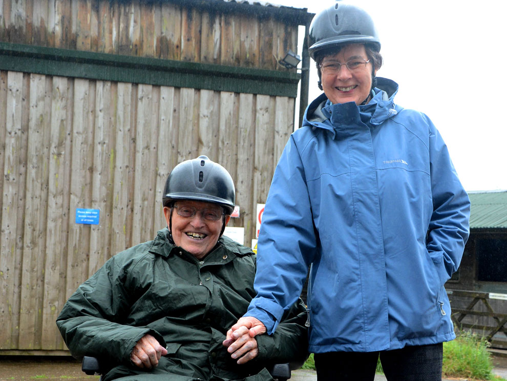 Mature man and woman, husband in wheelchair and wife standing beside him, both wearing coats and riding hats, smiling at the camera holding hands, outside