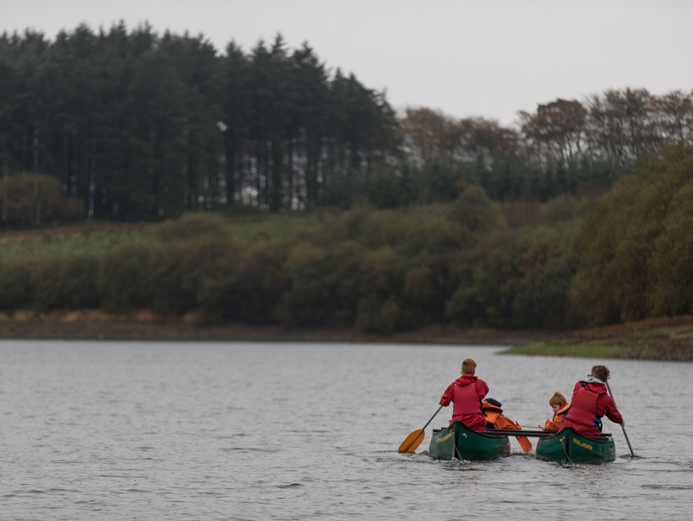 Family of four paddling in canoes on reservoir in North Devon