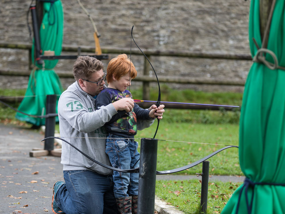 Man and child, father and son doing archery outside