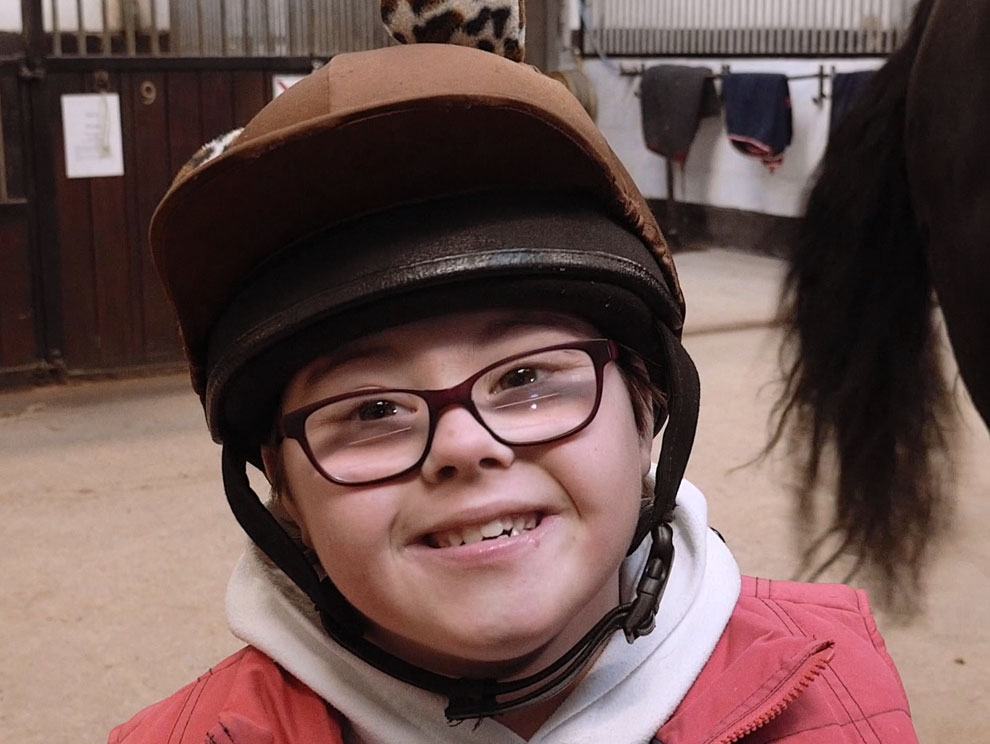 Smiling female child with Down Syndrome wearing spectacles and a riding hat in horse stables