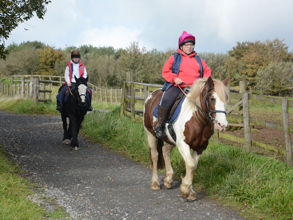Two horses being ridden down a countryside path by a female adult and female child