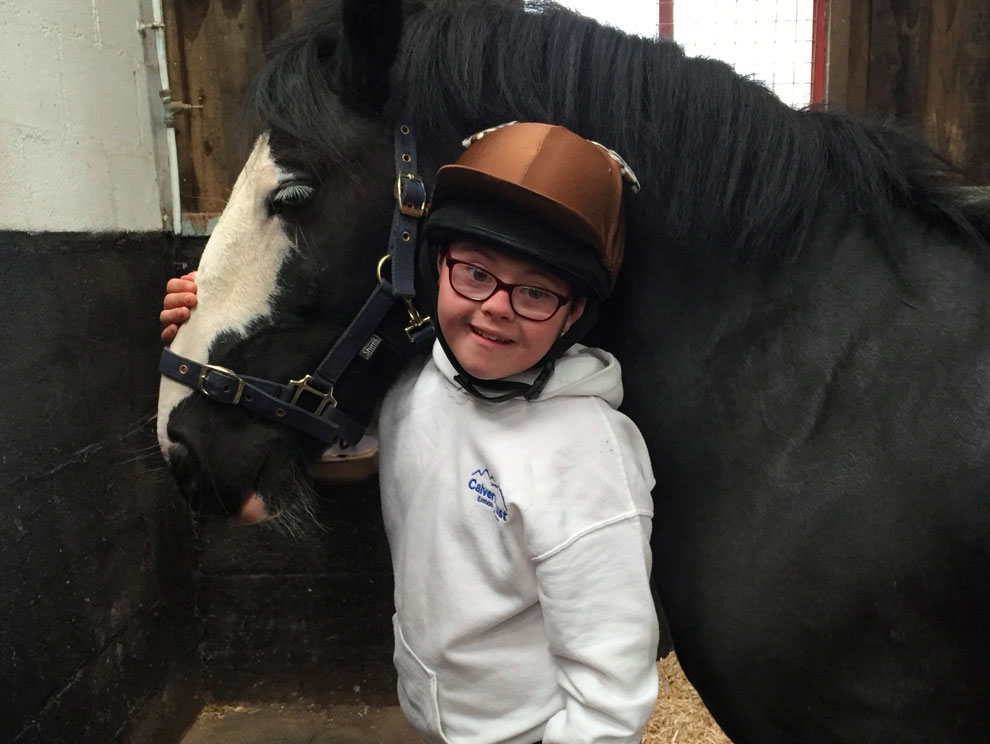 Female child with Down's Syndrome wearing a riding hat and spectacles, hugging a black and white horse in a stable whilst smiling and looking at the camera