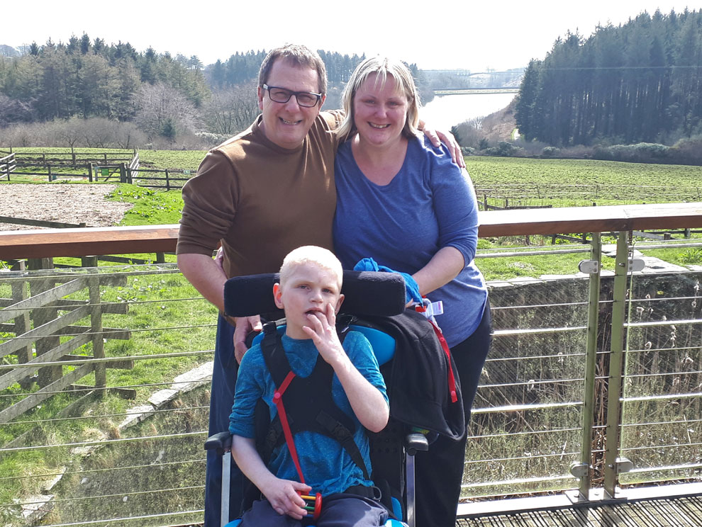 Man and woman with disabled child wheelchair user smiling in front of Wistlandpound Reservoir and countryside scenery