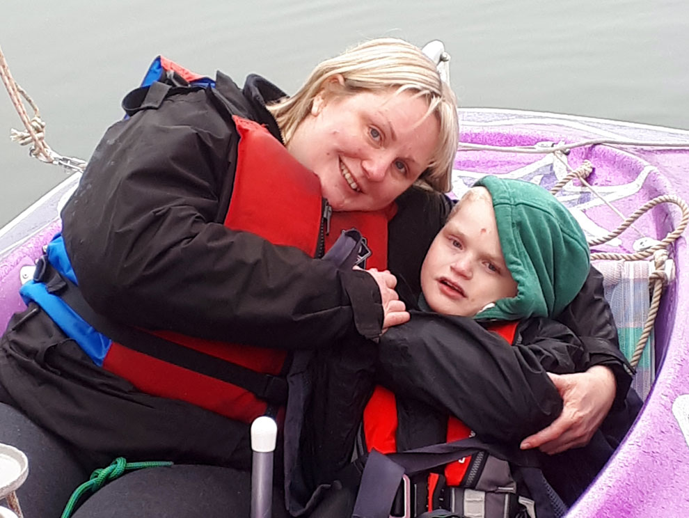 Smiling mum with arm around son, cuddling in a purple glittery sailing boat on lake water