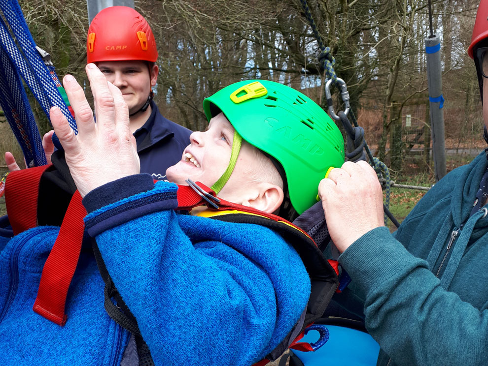 Smiling child wearing helmet and adaptive harness being hoisted by activities instructors in countryside