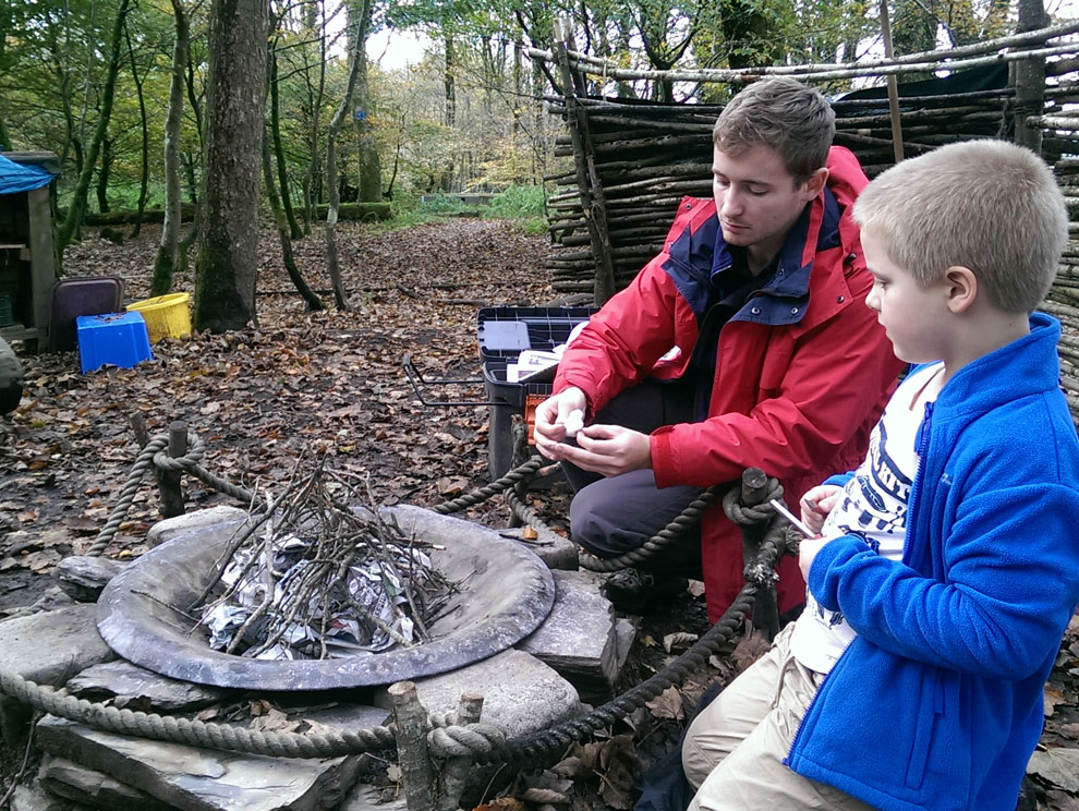 Man and child sat by an unlit fire in woodland forest with trees in background