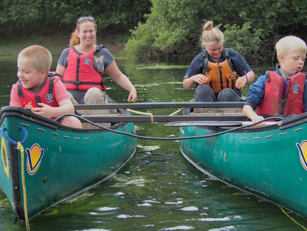 Smiling female adult and two male child guests and female activity instructor sitting in tandem canoes on water at Wistlandpound Reservoir in North Devon