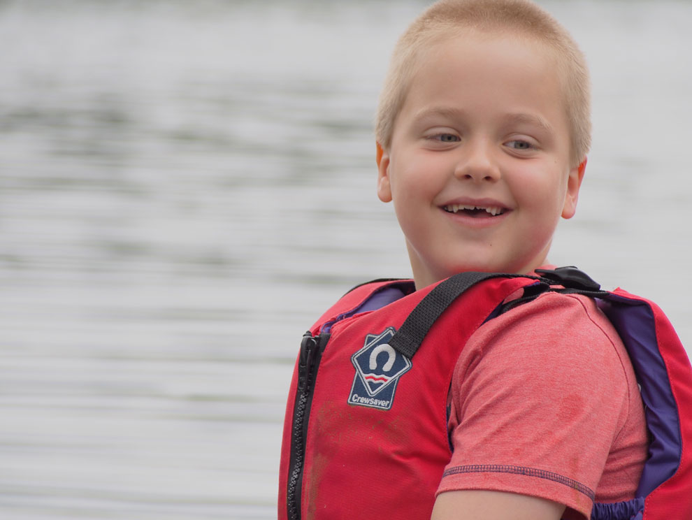Smiling child wearing a life jacket on the water