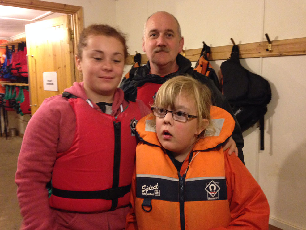 3 Calvert Trust Exmoor guests inside boathouse wearing lifejackets
