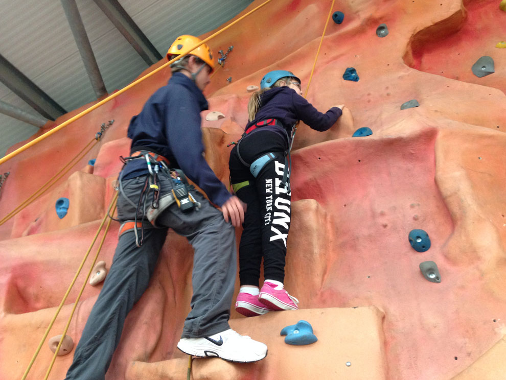 Female Child and male activities instructor using an indoor climbing wall with ropes and harnesses, wearing helmets