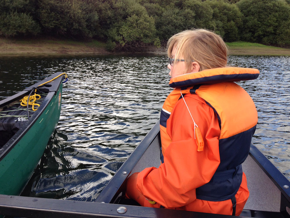 Female child with disability wearing a life jacket and waterproofs sitting in accessible tandem canoe on the lake