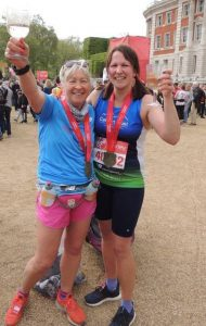 2 ladies in running clothing with winners medals and drinks