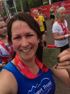 A lady with her London Marathon 2019 medal smiling at the camera