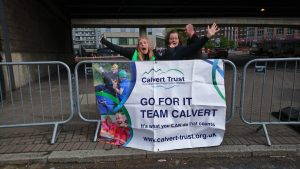 A banner with Calvert Trust logo and 'Go For It' message with two ladies smiling and waving arms in the air
