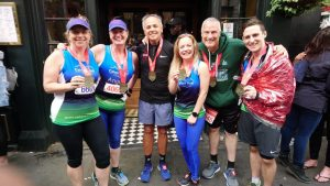 A group of London Marathon runners holding medals and smiling at camera