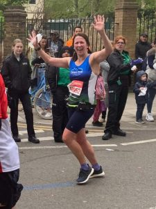 A lady running during the London Marathon 2019 with a crowd in the background, waving to the camera