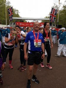 Man posing in a crowd with a medal around his next, the London Marathon finish line in the background