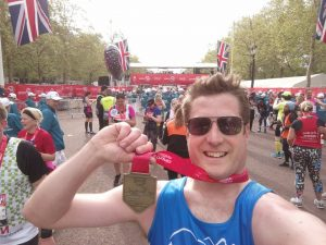 Man holding a medal from around his neck with the London Marathon 2019 finish line in the distance behind