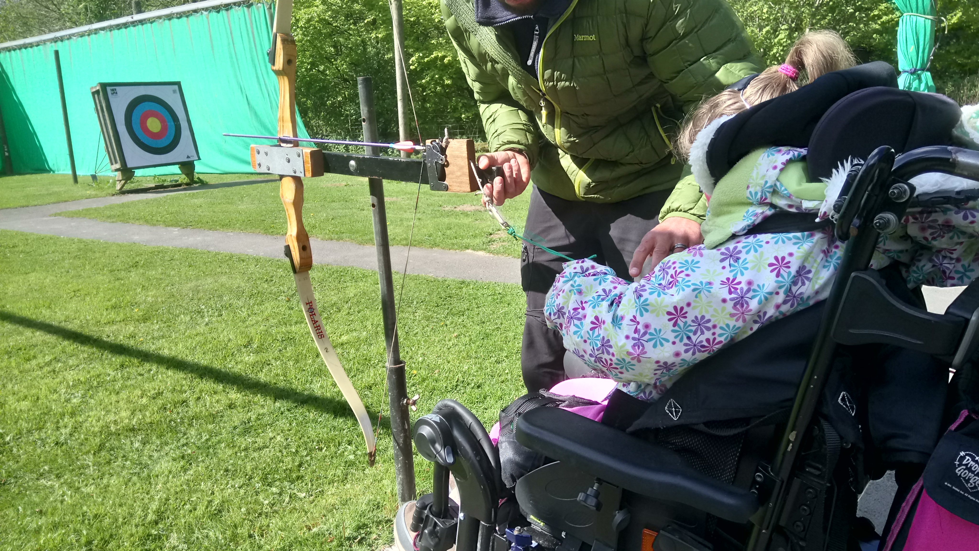 Little girl in wheelchair doing archery with help of a male instructor