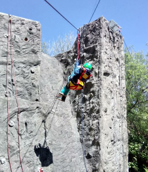 Girl in harness suspended in the air in front of a climbing wall