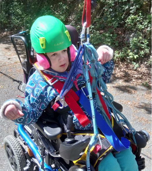 Little girl in wheelchair in safety gear and equipment being hoisted out the chair