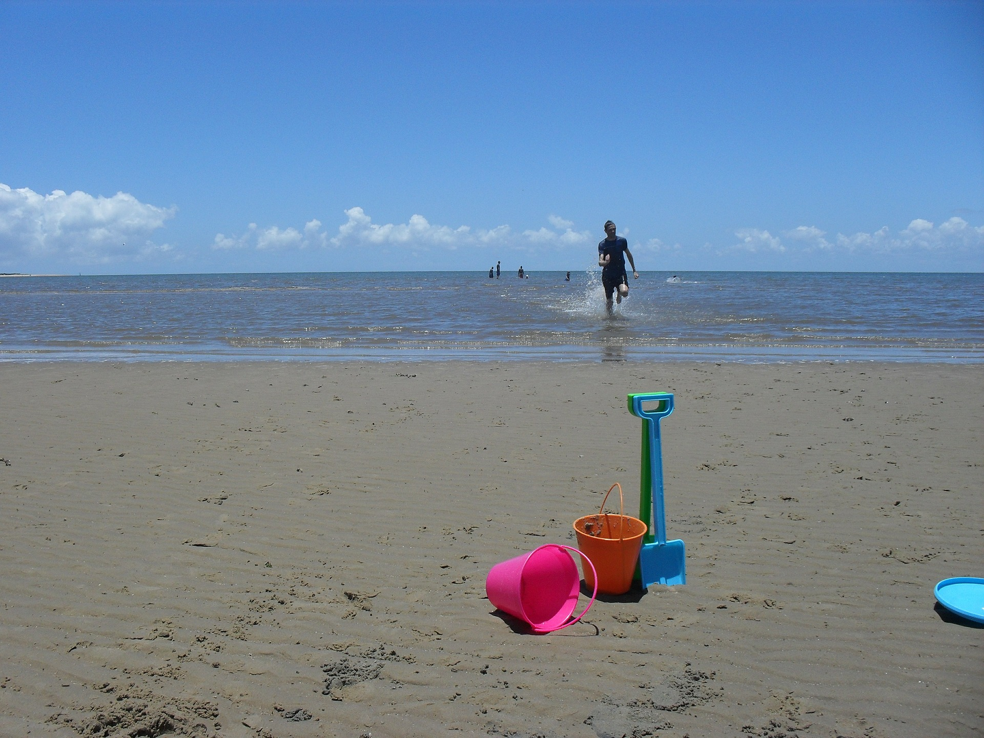 Buckets and spade on a beach with the sea in the background and a surfer running out the sea