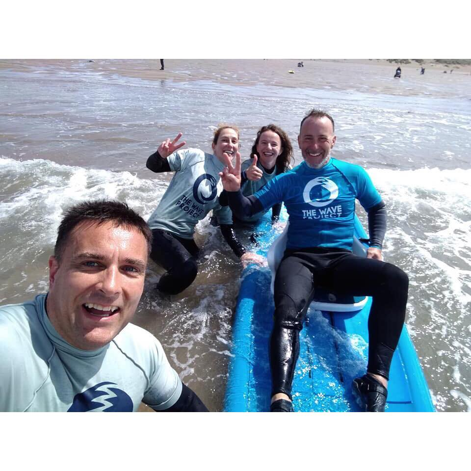 Four people in the sea and on a surfboard smiling and posing for the camera