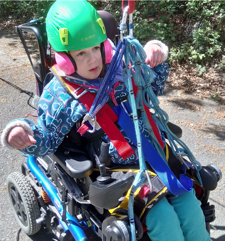 Girl in a wheelchair wearing helmet, being hoisted out of the seat by a harness
