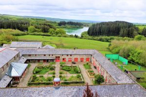 Ariel shot of Calvert Trust Exmoor; building and courtyard, fields and trees, reservoir in the distance